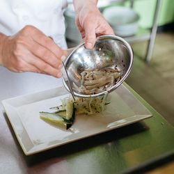 Chef Hewit adds cucumbers and onions tossed in sea salt, oil, and chili flake to the plate.