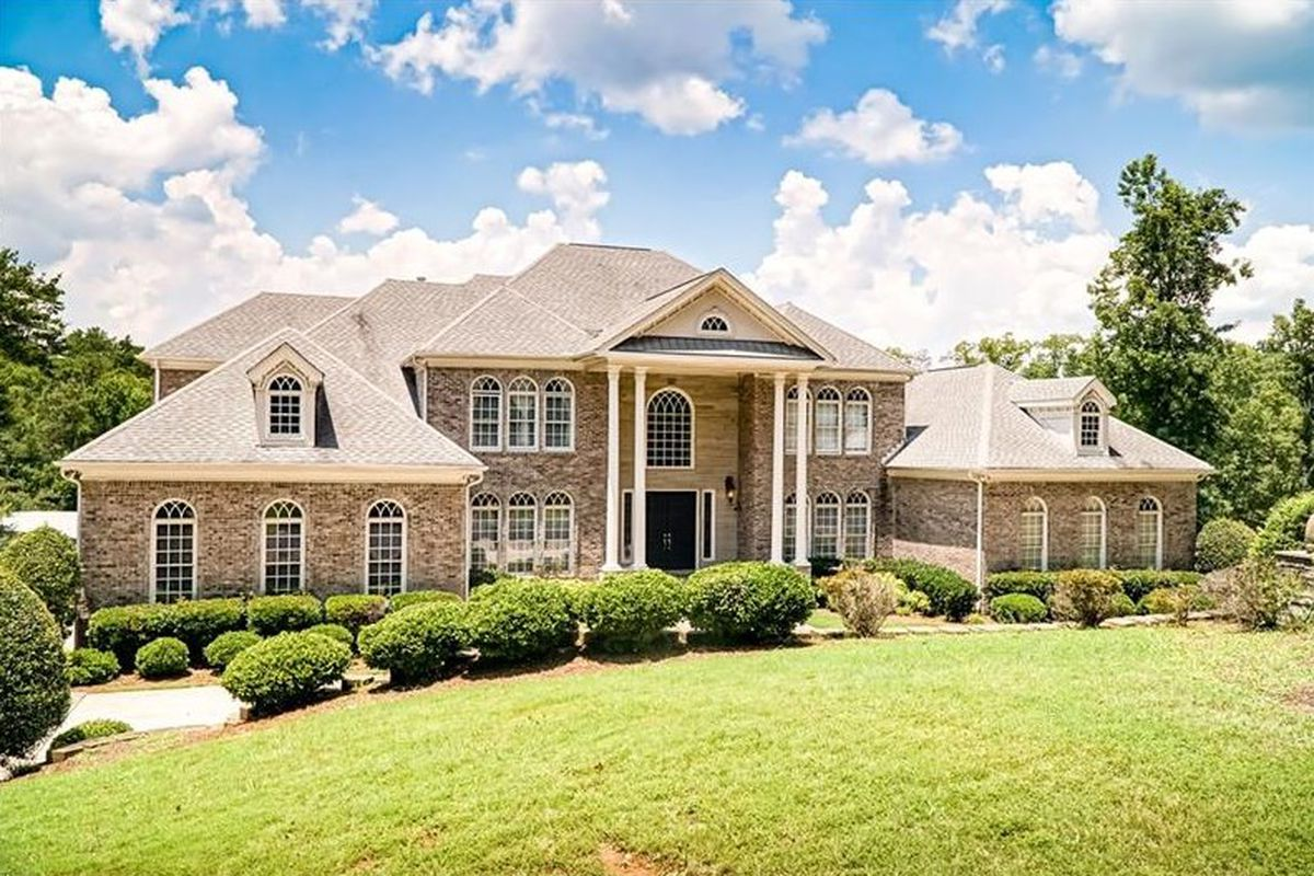 Brick mansion with white columns and green lawn.