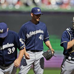 Milwaukee Brewers shortstop Jean Segura, left, pitching coach Rick Kranitz (39) and catcher Jonathan Lucroy, right, depart the mound after talking with starting pitcher Marco Estrada (41) during the fourth inning of a baseball game against the Washington Nationals at Nationals Park, Monday, Sept. 24, 2012, in Washington. The Nationals won 12-2.