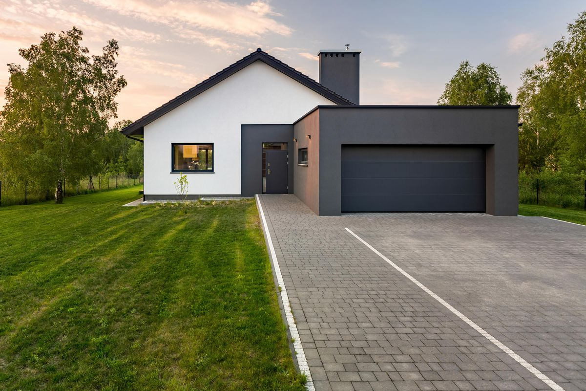 A modern house with a cobblestone driveway.