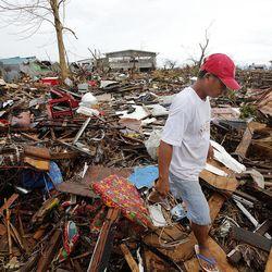 Tony Ballais, who lost his home in a typhoon, walks through rubble in Tacloban, Friday, Nov. 22, 2013.