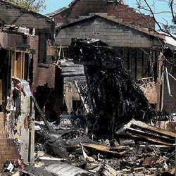 Heavy damage remains at the Mayfair Mews apartment complex Saturday, April 7, 2012, in Virginia Beach, Va., after a Navy fighter jet crashed there Friday. The Navy and civilian authorities have just begun their investigation into the crash of the F/A-18D fighter that hit the complex.