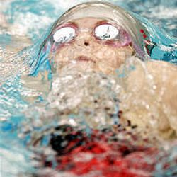 Annika Bergesen of Kearns High School competes in the 100-yard backstroke against teams from Skyline, Alta and Murray high schools.