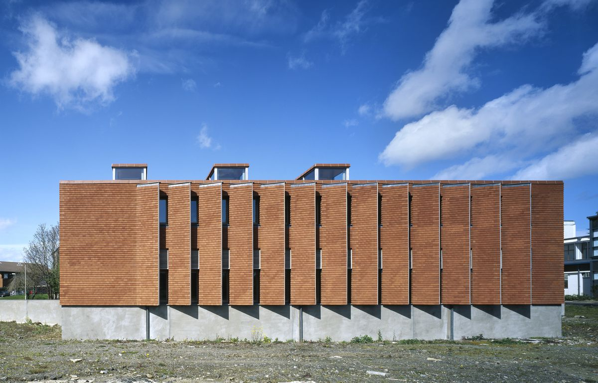 A rectangular brick building on a concrete foundation with fin-like openings on the facade.