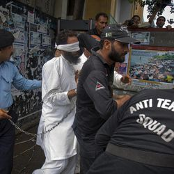 Pakistani police commandos escort blindfolded Muslim cleric Khalid Chishti, center, after his court appearance in Islamabad, Pakistan on Sunday, Sept. 2, 2012.  In the latest twist in a religiously charged case that has focused attention on the country's harsh blasphemy laws, Pakistani police arrested  Chishti who they say planted evidence in the case of a Christian girl accused of blasphemy.