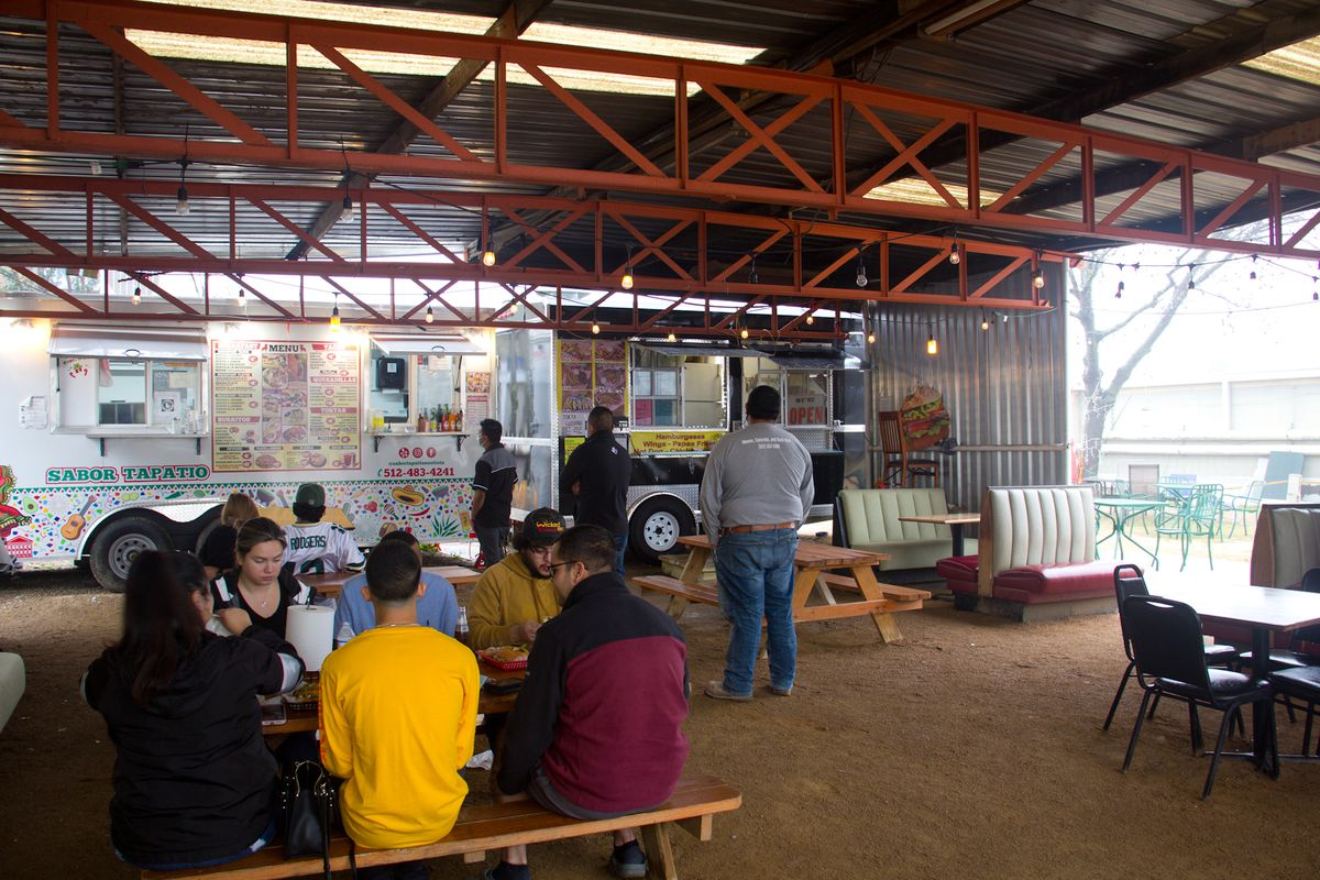 A covered dining area with a metal and wooden awning and two food trucks in the background, there are people waiting to order food at the trucks, and there is a group of people sitting at a picnic table