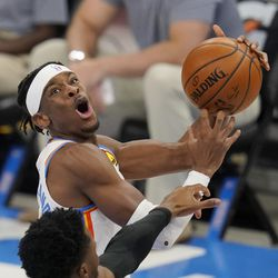 Oklahoma City Thunder guard Shai Gilgeous-Alexander, top, goes to the basket while defended by Utah Jazz guard Donovan Mitchell during the second half of an NBA basketball game in Oklahoma City, Monday, Dec. 28, 2020.