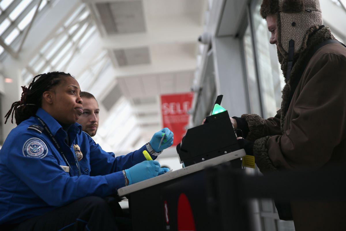 A TSA agent checks a traveler's identification at a special TSA Pre-check lane at LaGuardia Airport.
