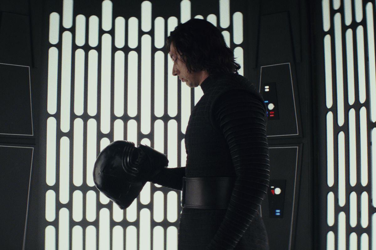 Adam Driver as Kylo Ren, looking at his helmet.