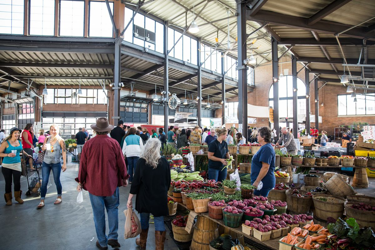 People gather next to a fruit stand inside the Eastern Market sheds.
