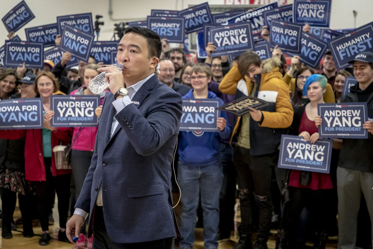 Yang standing in front of crowd of supporters holding signs; he's drinking from a bottle of water.