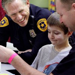 Salt Lake police detective Dennis McGowan chats with Sean Lance and his father, Tony, at Primary Children's Medical Center in Salt Lake City on Thursday, Jan. 19, 2012. Sean is recovering from pneumonia.