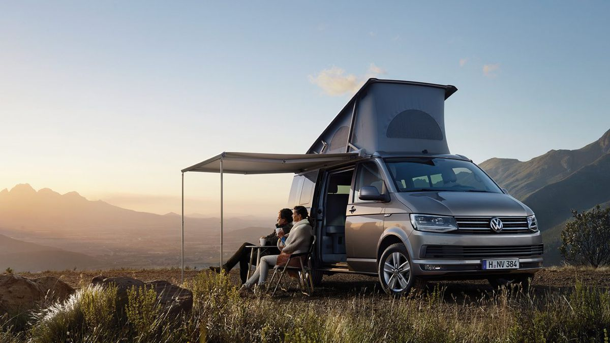 A brown camper van. There is an inflatable tent on the roof of the van. There is an awning attached to the van. A man and a woman are sitting in chairs under the awning. There are mountains in the distance.