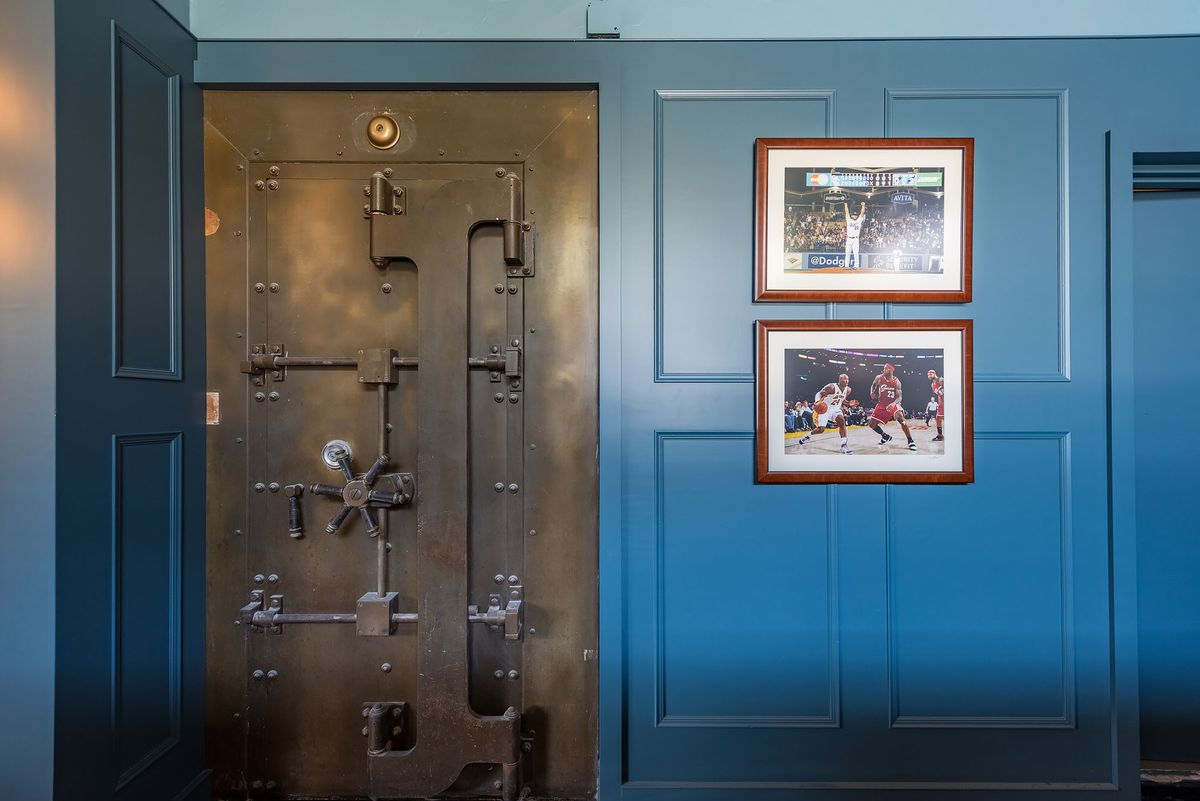 Vault door and sports photos on a blue wall at The Greyhound.