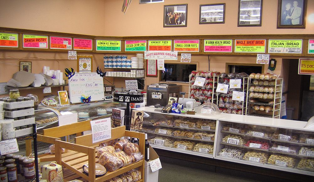 The bakery counter at Bommarito has pink, yellow, and green tagboard signs over the top.
