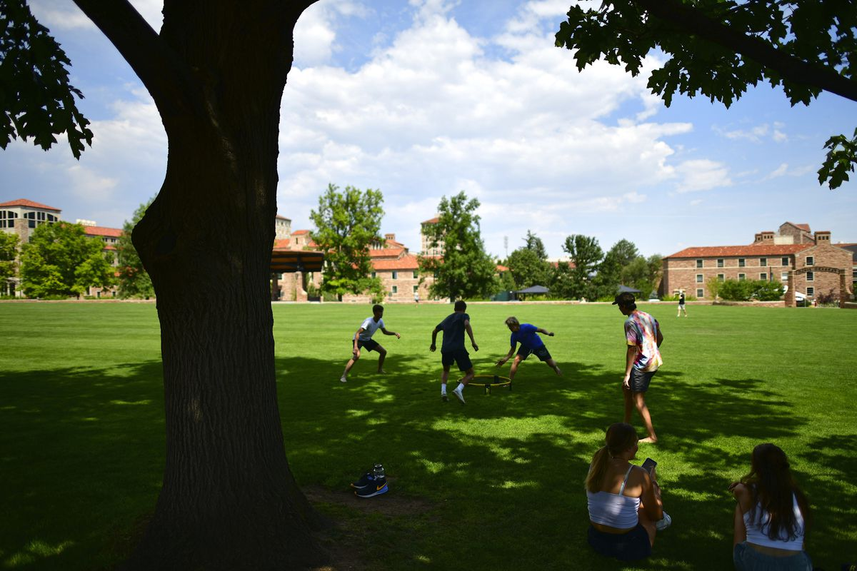 Students play on the lawn at the University of Colorado at Boulder campus on a bright sunny day.