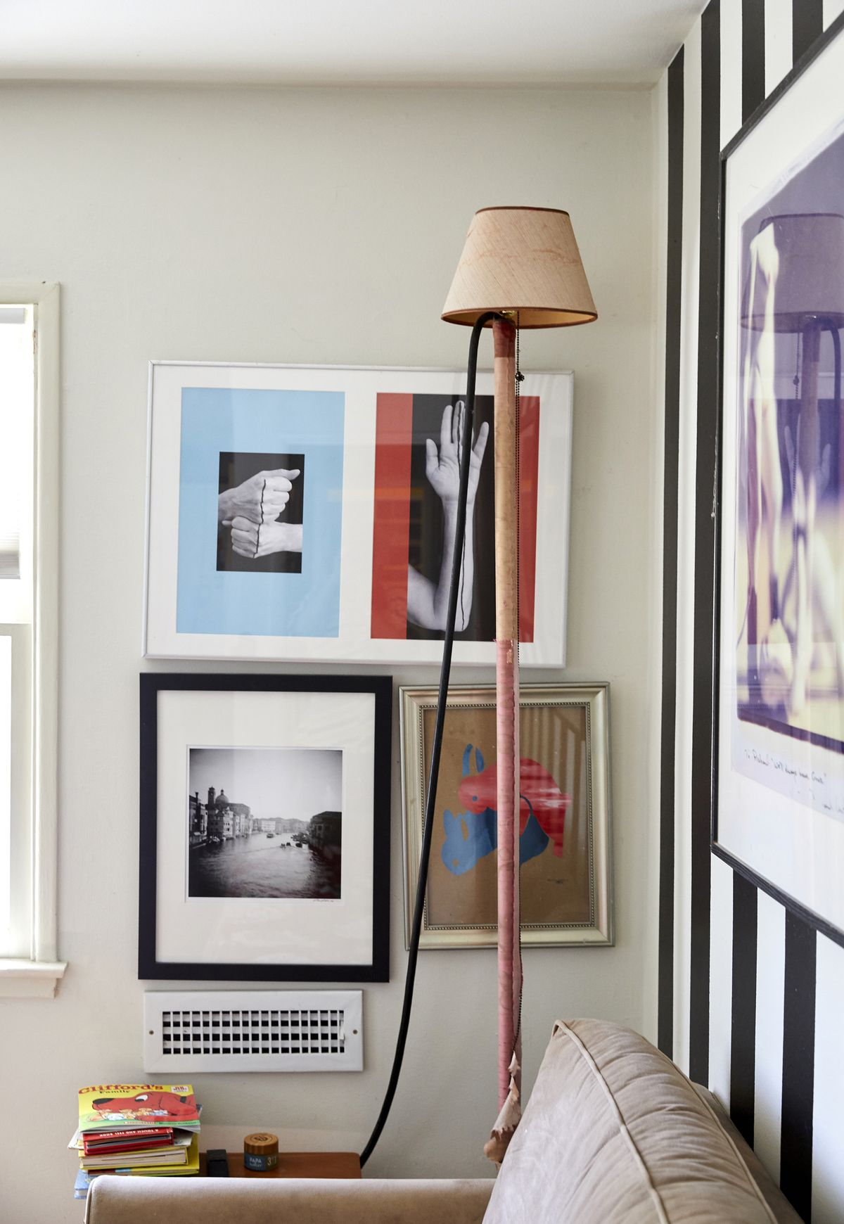 The corner of a room with a painted white wall that has many framed works of art hanging on it. There is a tall floor lamp next to a couch.