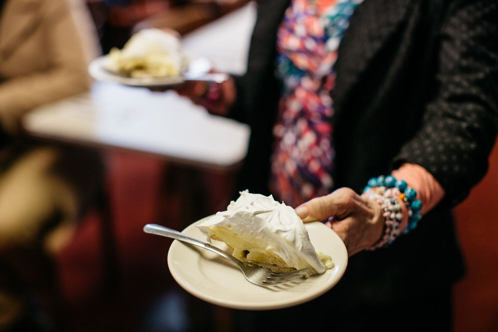 A waitress with a black jacket, a pink patterned shirt, and blue bracelets carries a slice of banana cream pie in each hand.