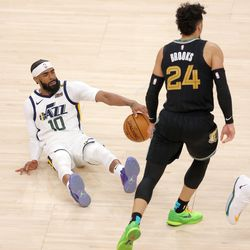 Utah Jazz guard Mike Conley (10) is knocked to the floor by Memphis Grizzlies forward Dillon Brooks (24) as the Utah Jazz and the Memphis Grizzlies play in game one of their NBA playoff series at Vivint Arena in Salt Lake City on Sunday, May 23, 2021.