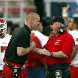 Former Utah and current Utah State coach Gary Andersen celebrates with coach Ron McBride after Utah beat USC.