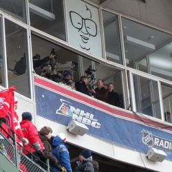 """Hawks and Cubs legends lead the crowd in """"Take Me Out To The Hockey Game"""" under the watchful eye of the Harry Caray caricature"""