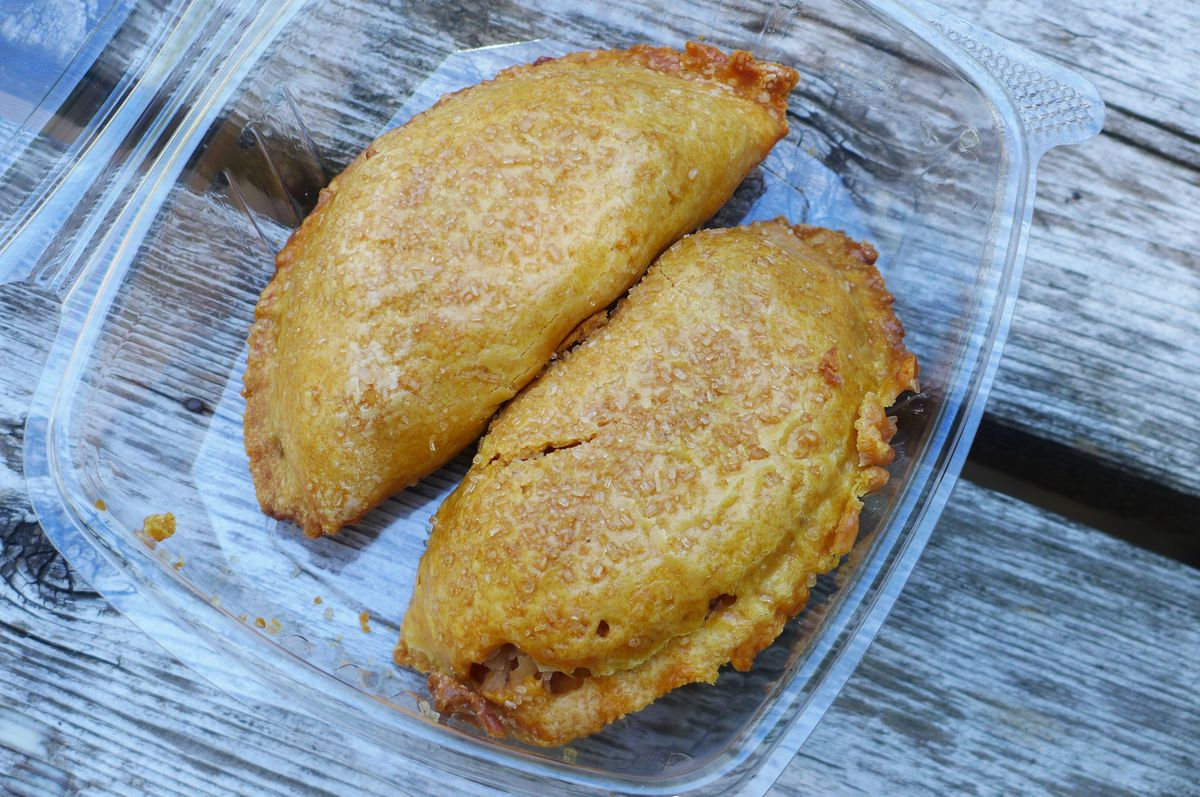 A pair of empanadas on a wooden table.