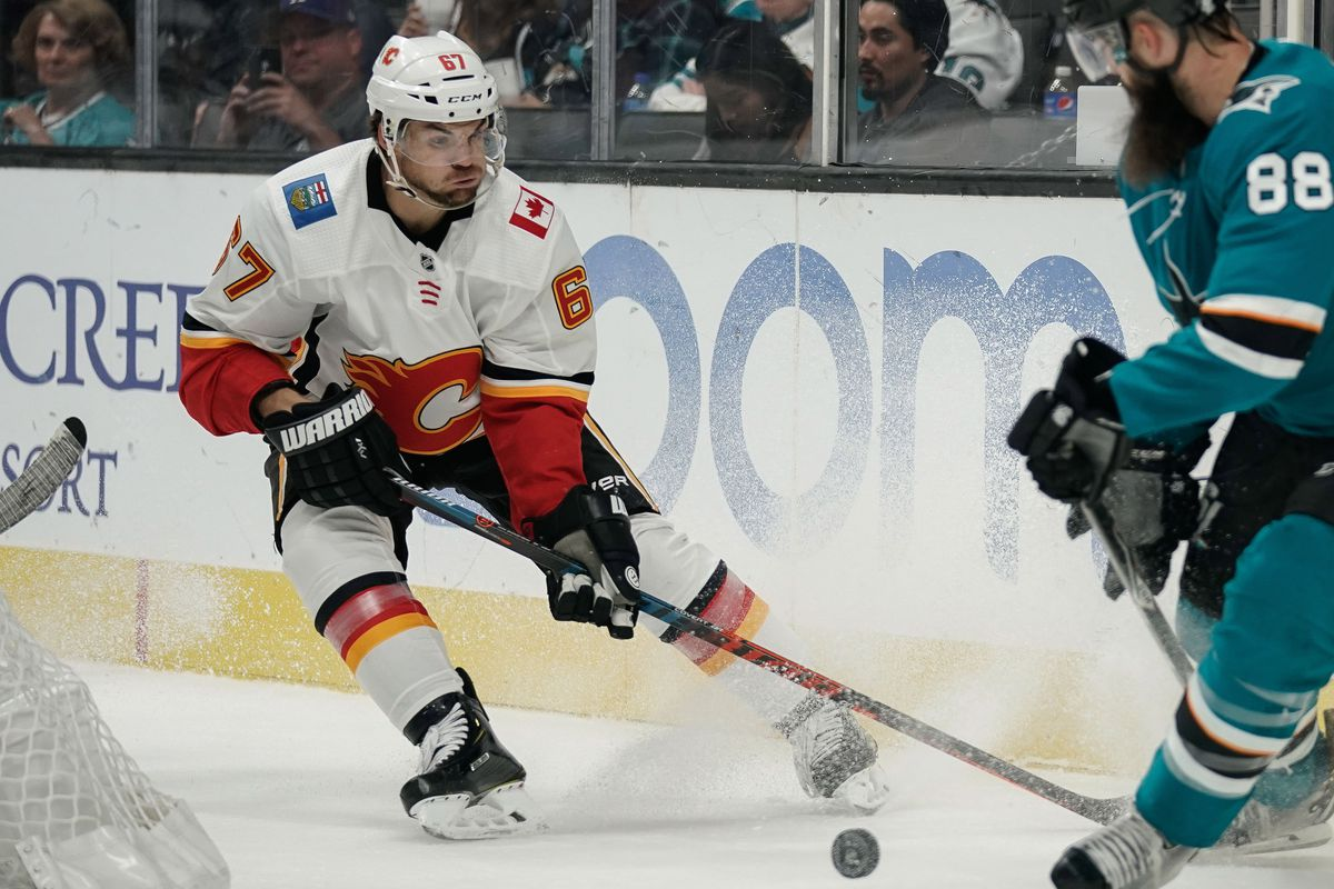 Sep 27, 2018; San Jose, CA, USA; Calgary Flames right wing Michael Frolik (67) and San Jose Sharks defenseman Brent Burns (88) fight for control of the puck during the third period in SAP Center at San Jose.