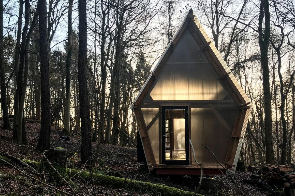 Small gabled-roof structure with corrugated steel and polycarbonate walls in woodland site.