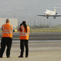 FILE - Runway workers watch as the first commercial flight to Ogden by Allegiant Air, approaches the runway at the Ogden Hinckley Airport Thursday, September 20, 2012. Utah residents will soon be able to fly from Ogden to Las Vegas and Los Angeles.