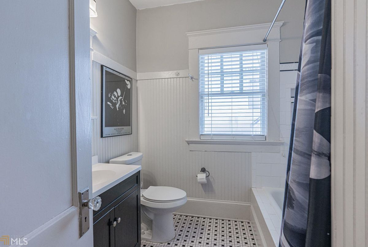 A white and black master bathroom with tile.