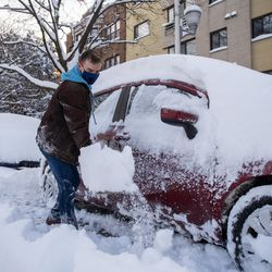 Michael Svabek digs his car out of the snow in the Edgewater neighborhood, Tuesday morning, Feb. 16, 2021, after a snowstorm dumped over a foot of snow in Chicago starting Sunday night. Snow is expected to continue to fall until Tuesday night.