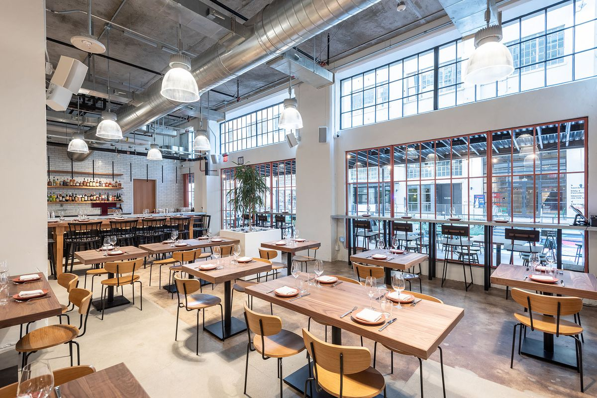 Inside Manufactory at the Row, with tall open windows and wooden tables and chairs and a bar in the background.