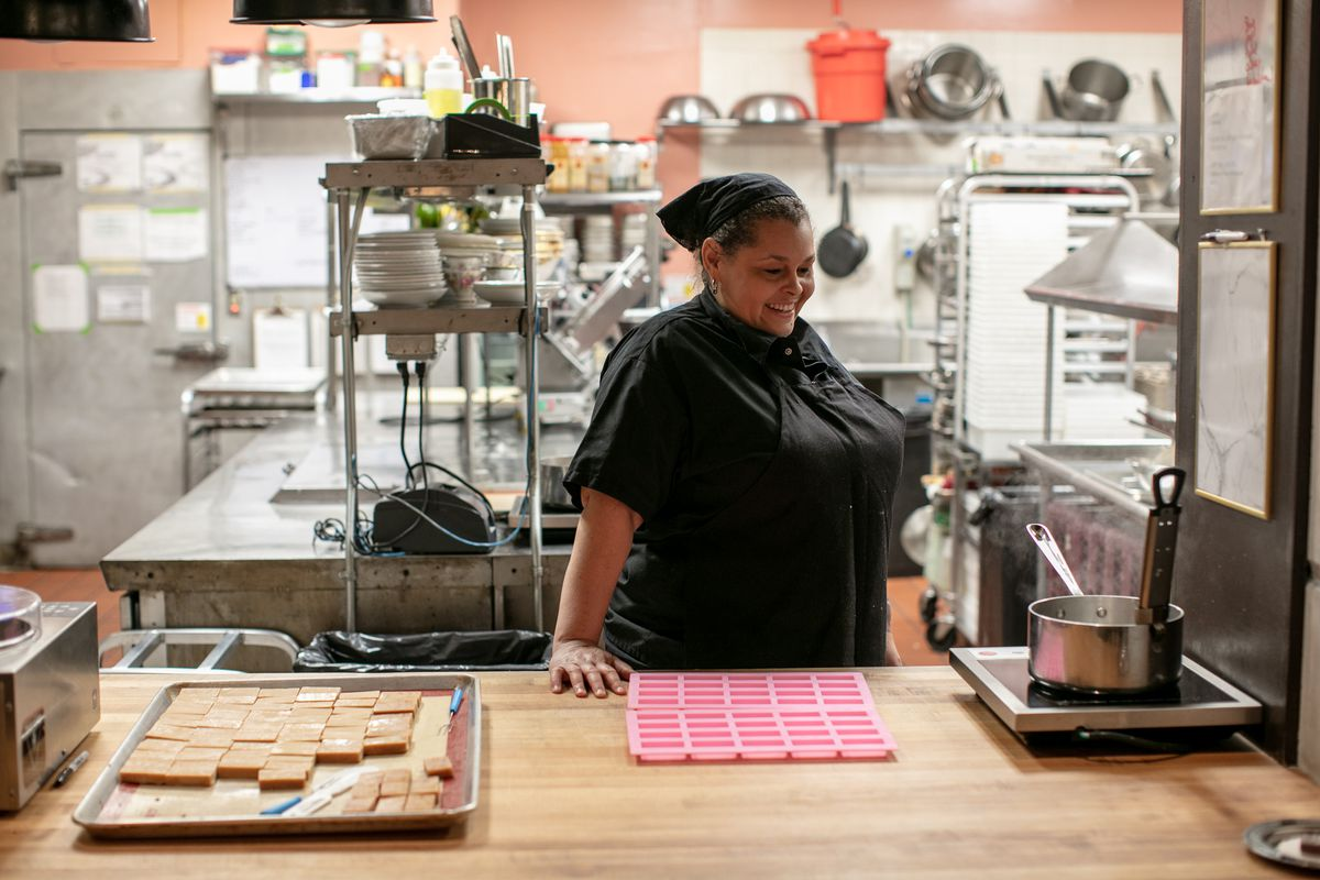 Monica greer wearing black, smiles behind the counter in the Lady of the House kitchen as she makes candy bars for Candy Bar at the Siren Hotel.
