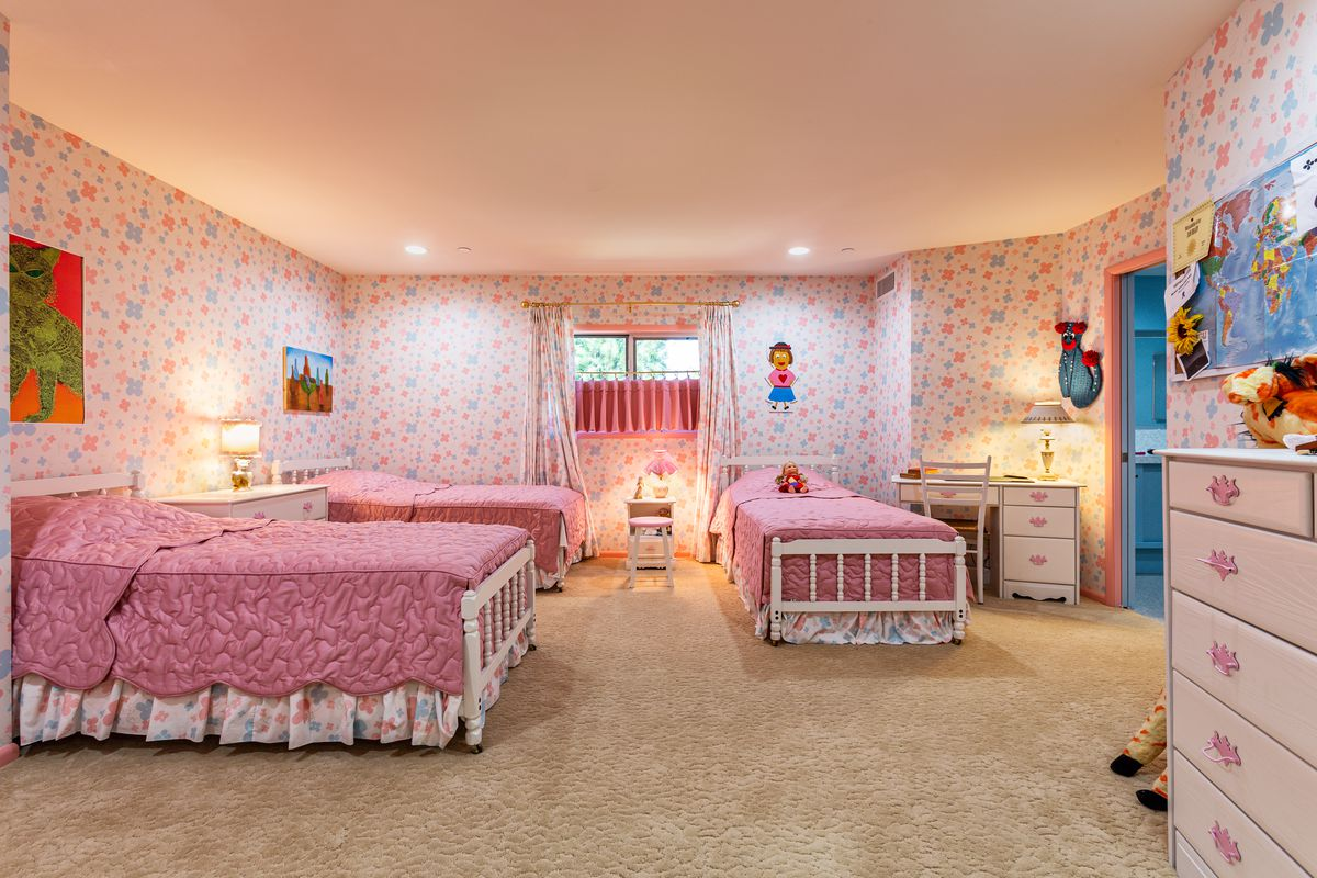 A bedroom with pink and purple flowered wallpaper and matching curtains. Three twin beds with white frames and pink quilt coverlets.