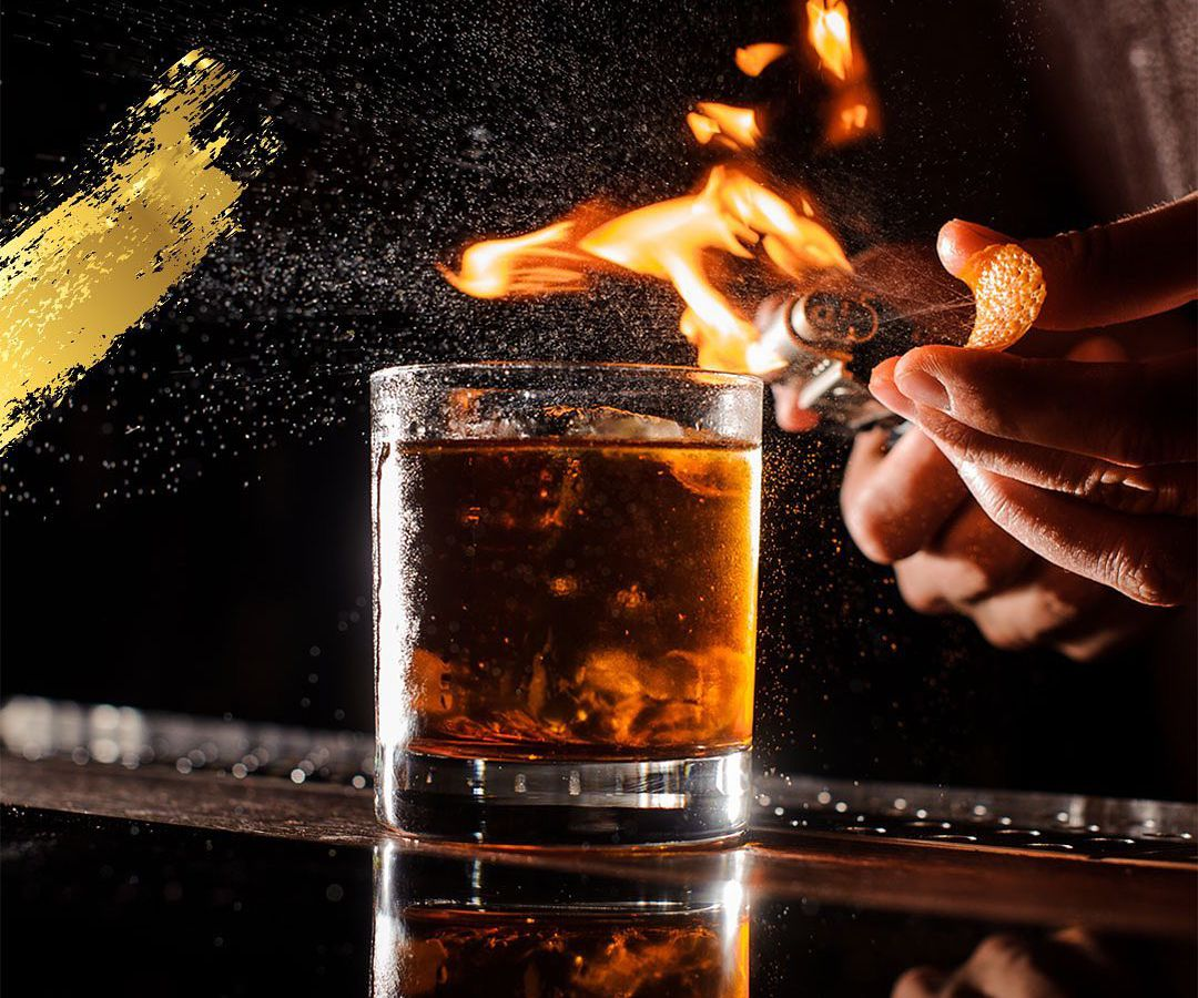 A brown cocktail lit on fire.