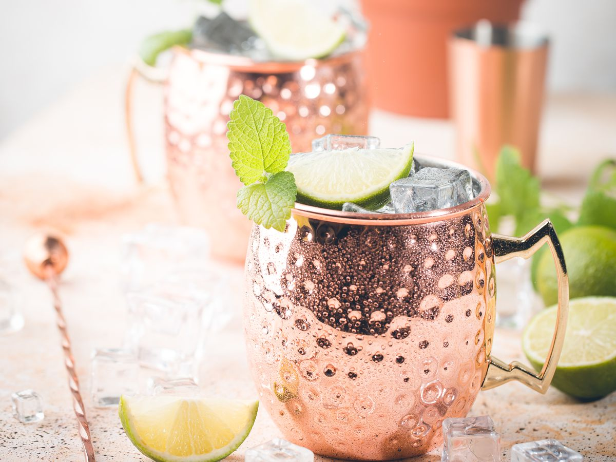Moscow Mules cocktails in copper mugs with a white stone background.