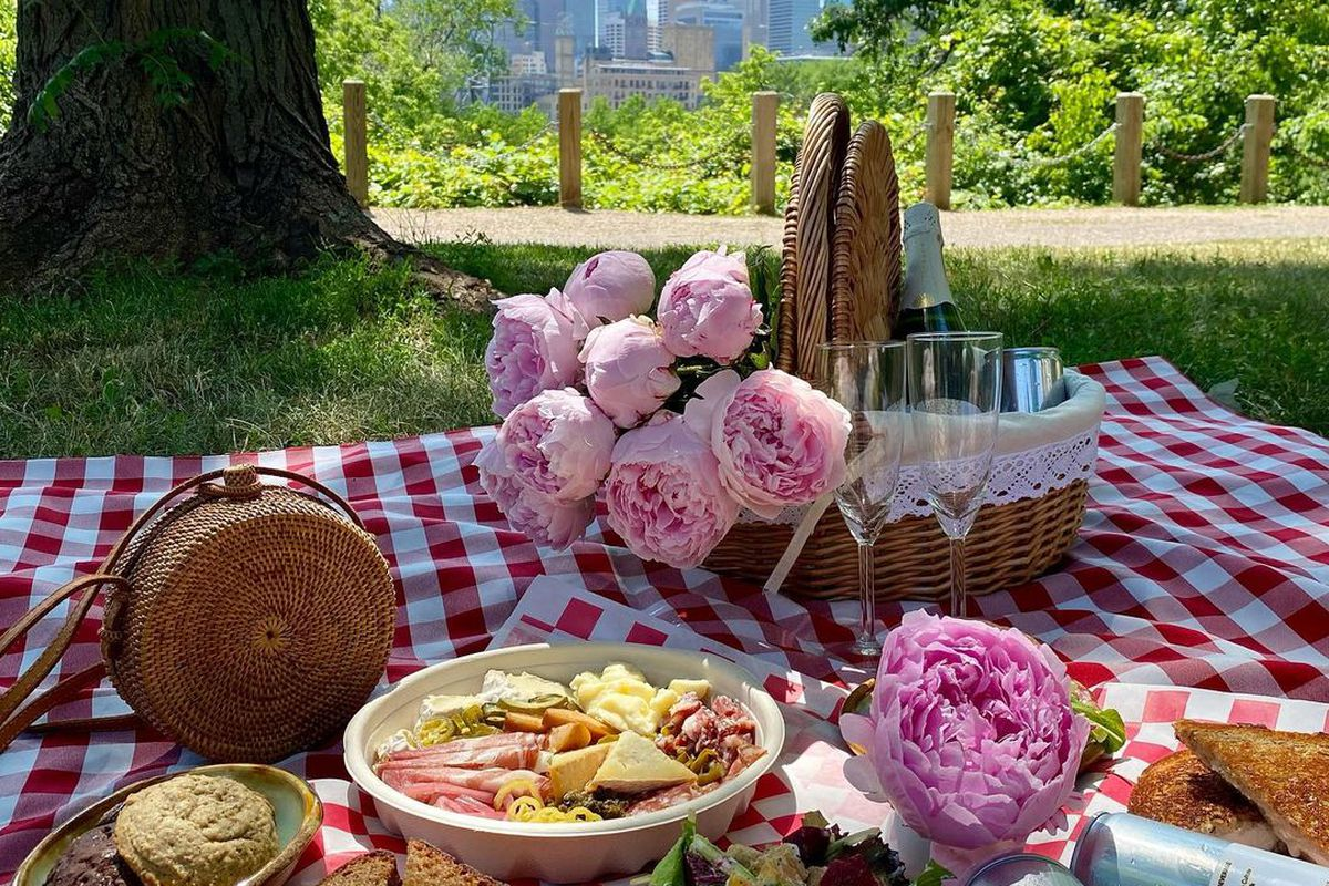 A picnic spread of peonies, sandwiches, salad and canned beverages on a red and white checkered blanket in a park.