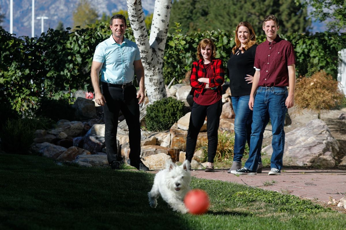 The Torkildsons — father Adam, daughter Katrina, mother Adrienne and son Noah — play with their dog Missy in the backyard of their house in American Fork on Sunday, Oct. 3, 2021