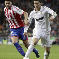 Real Madrid's Cristiano Ronaldo from Portugal vies for the ball with Sporting Gijon's Alberto Tomas Botia during a Spanish La Liga soccer match at the Santiago Bernabeu Stadium in Madrid, Spain, Saturday, April 14, 2012.