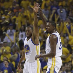 Golden State Warriors forward Andre Iguodala (9) and forward Kevin Durant (35) react after scoring against the Cleveland Cavaliers during the first half of Game 1 of basketball's NBA Finals in Oakland, Calif., Thursday, June 1, 2017.
