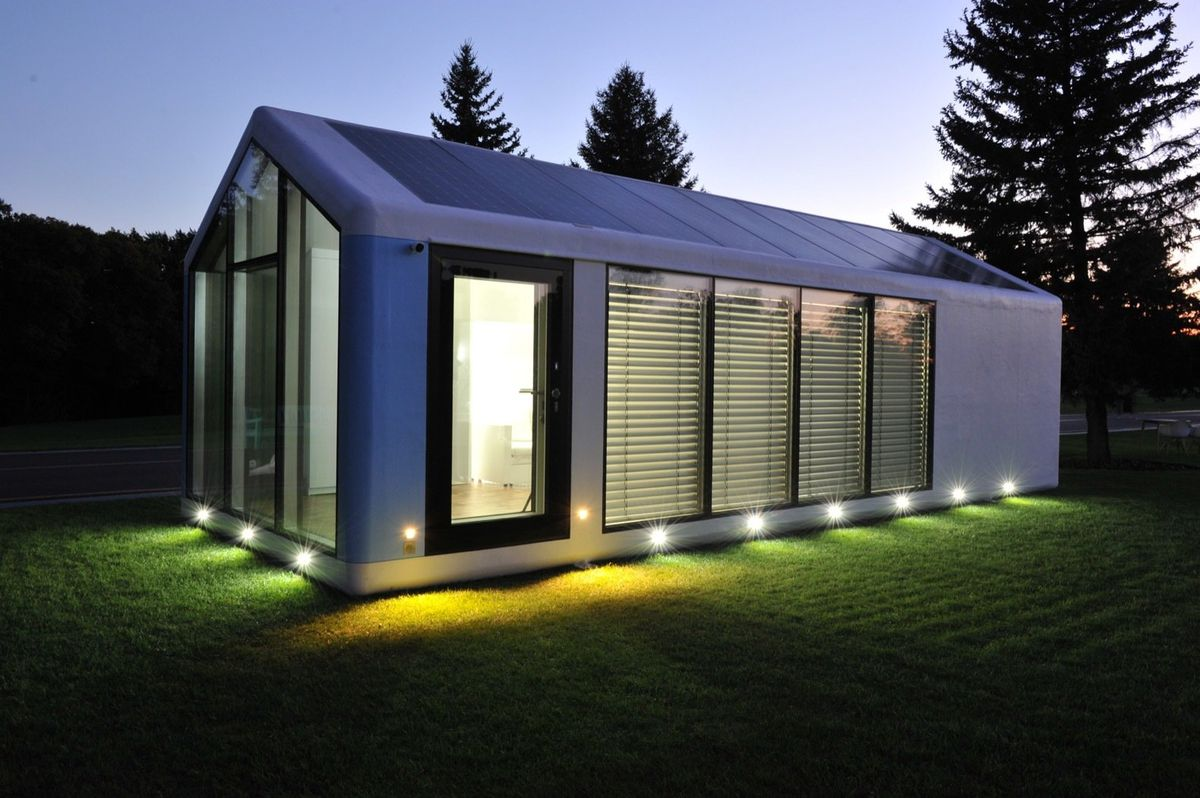 Pitch-roofed house with many large windows sits on a grassy plot of land. A series of lights placed at the bottom of the facade illuminates the home.