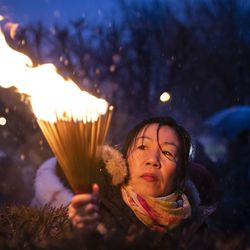 A woman lights a batch of incense as hundreds gather for a vigil in a parking lot in the 2000 block of South Wells in Chinatown, where Huayi Bian and Weizhong Xiong were shot to death, Wednesday, Feb. 12, 2020. Bian and Xiong were killed during an apparent robbery, for which Alvin Thomas faces two counts of first-degree murder.