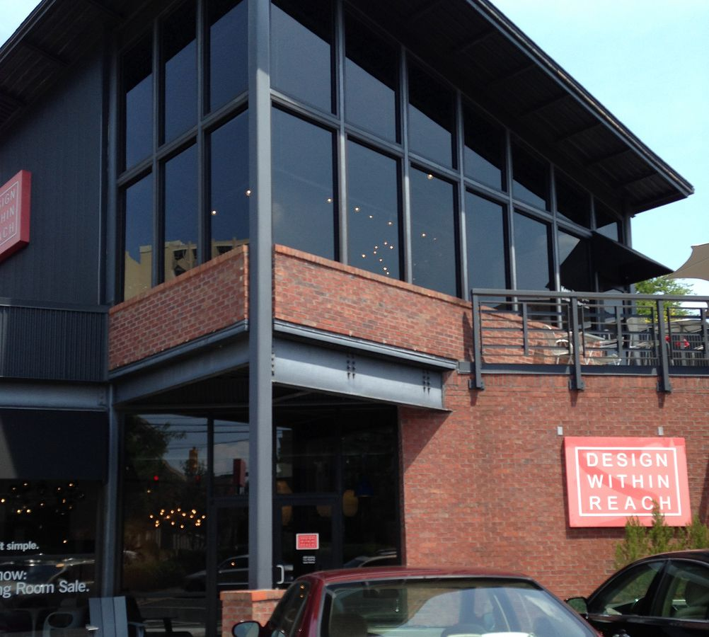The exterior of a furniture store. The facade is red brick with multiple windows. There is a red sign with words that read: Design within Reach.