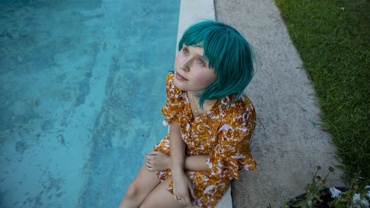 a young woman in a blue wig sits by a pool