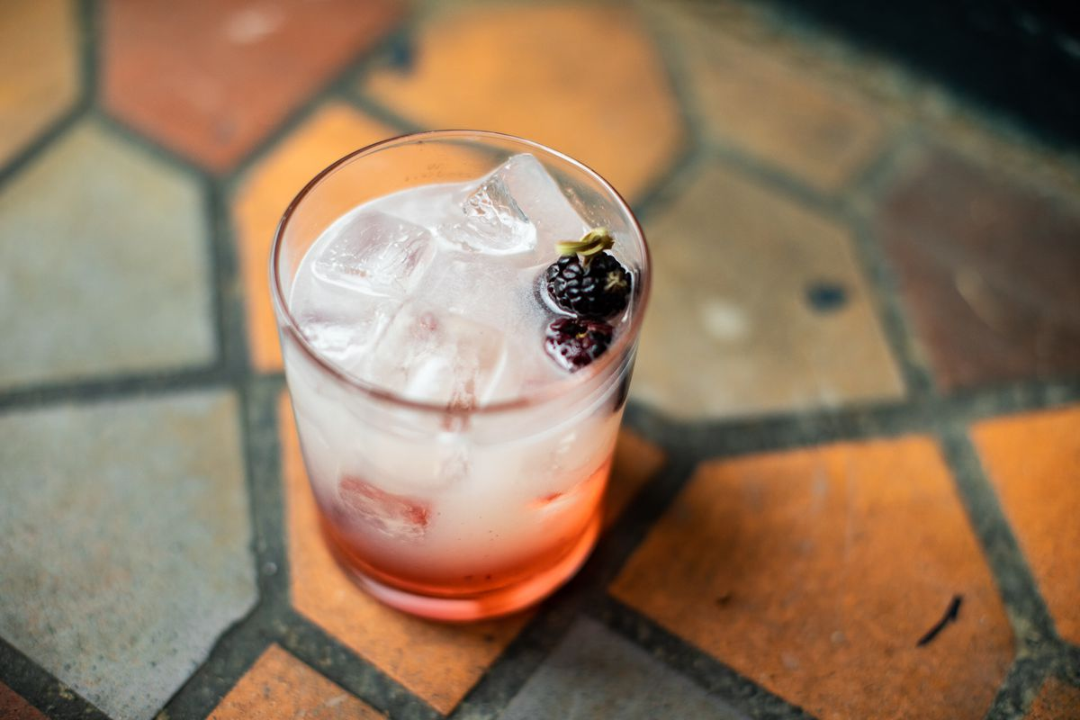 A cocktail with ice, a purple liquor, and a blackberry garnish sits on a tile floor.