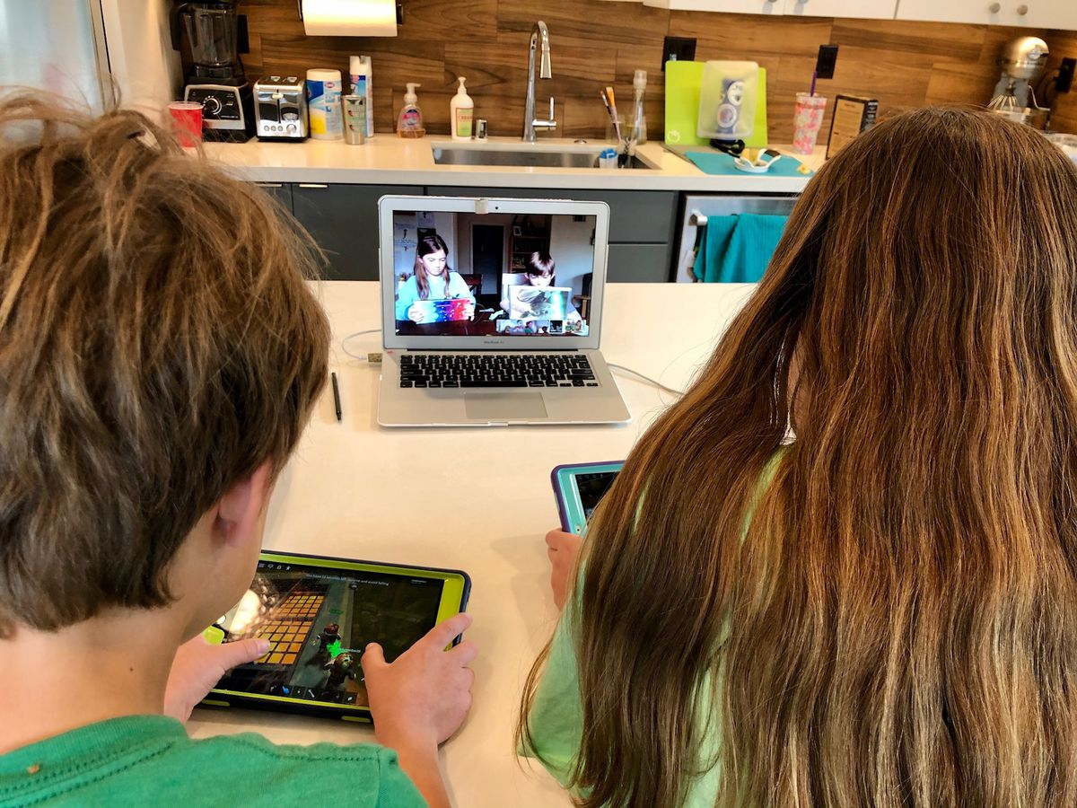 Two children play Roblox on mobile devices, while a laptop connects them to a Hangout call with their friends