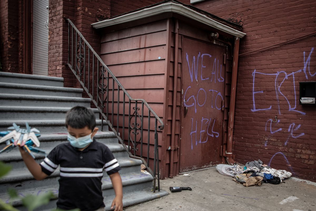 """A child plays with a toy plane outside of a church where graffiti says """"We all go to hell"""""""