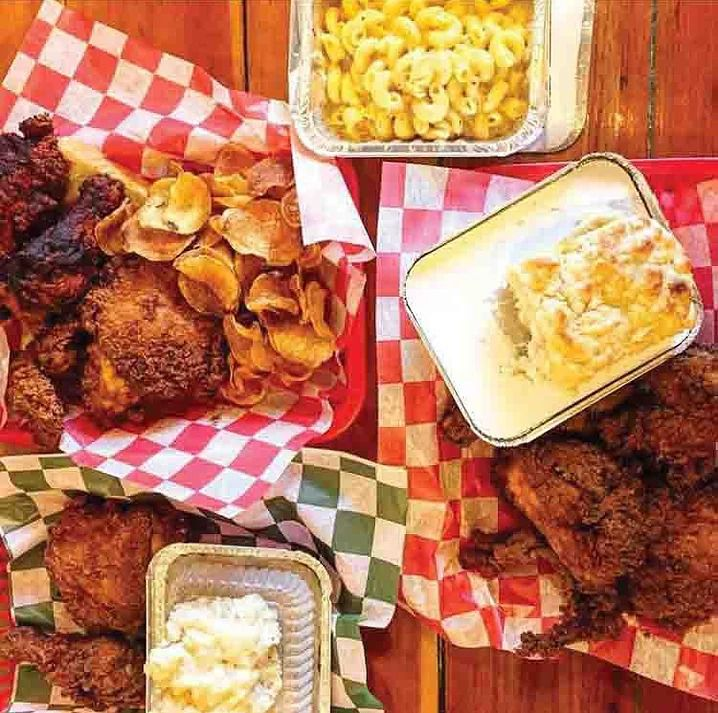 Baskets of fried chicken with biscuits, chips, and mac and cheese.
