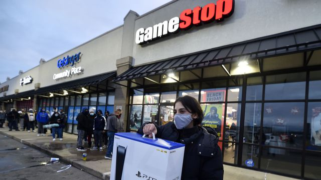 A man wearing a face mask leaves GameStop with the new PlayStation 5
