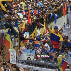 ALTERNATIVE CROP OF XFLL104 - Opposition presidential candidate Henrique Capriles, center, gestures to supporters during a campaign rally in Caracas, Venezuela, Sunday, Sept. 30, 2012. Presidential elections in Venezuela are scheduled for Oct. 7.